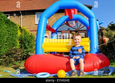 Kind spielt in einer bunten Hüpfburg - Stockfoto