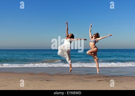 Zwei junge Tänzerinnen, die Luft am Strand springen - Stockfoto