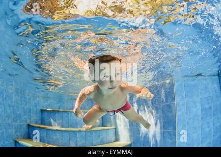 Lächelnde Kind schwimmen mit Spaß - unter Wasser zu springen Sie und Tauchen Sie tief nach unten. Familie Gesundheit, - Stockfoto