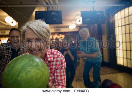 Begeisterte Frau mit Freunden auf der Kegelbahn Kegeln - Stockfoto