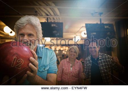 Mann mit Freunden auf der Kegelbahn Kegeln - Stockfoto