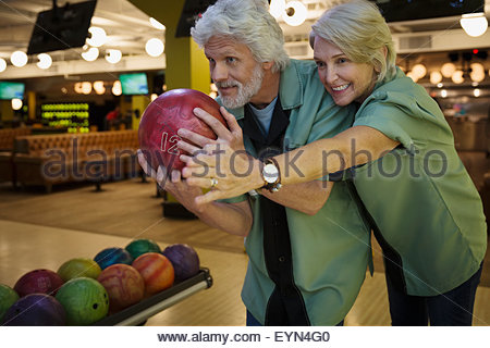 Ehefrau leitende Ehemann auf Kegelbahn Kegeln - Stockfoto