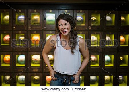 Porträt lachender Junge Frau in der Nähe von Bowling-Kugel-Schließfächer - Stockfoto