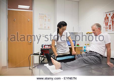 Physiotherapeut mit Kompression Knie wickeln auf Patienten - Stockfoto