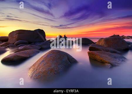 Farbenprächtigen Sonnenuntergang am Rande eines ruhigen Strand - Stockfoto