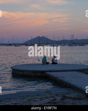 Romantisch zu zweit am Meer sitzen auf einem Anlegehafen mit einem romantischen Picknick in Puerto Pollensa - Stockfoto