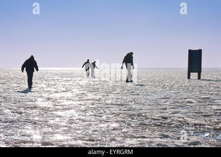 Vier jungen machen eine sorgfältige Wanderung auf einem zugefrorenen See - Stockfoto