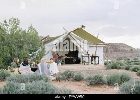 Gruppe von Freundinnen genießen Sie eine Mahlzeit in einer Wüste von einem großen Zelt im Freien.