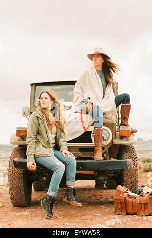Zwei Frauen sitzen auf der Vorderseite eines Jeeps auf einem Roadtrip. - Stockfoto
