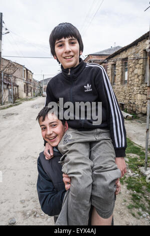 Georgischen Jungs aus Gori, Georgia Asien hängen an einer Straßenecke heben einander auf Spaß und Gestikulieren. - Stockfoto