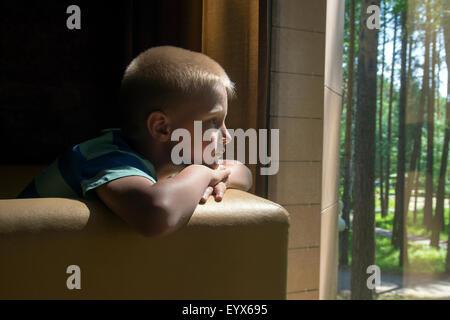 Kind (junge) in der Nähe eines Fensters depressiv traurig aufgeregt warten langweilig - Stockfoto