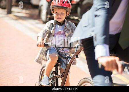 Porträt, lächelnde junge Reiten Fahrräder an sonnigen Straße - Stockfoto