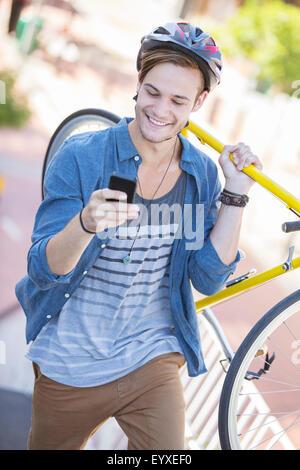 Junger Mann mit Helm mit Fahrrad und SMS auf Handy - Stockfoto