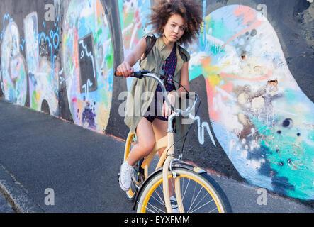 Porträt Ernst Frau mit Afro auf dem Fahrrad neben urban Graffitiwand - Stockfoto