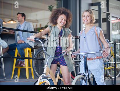 Porträt, Lächeln Frauen auf Fahrrädern vor café - Stockfoto