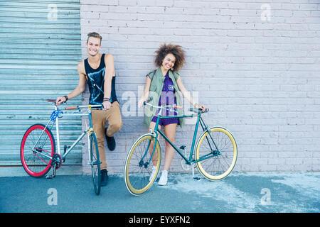 Porträt junger Mann und junge Frau mit Fahrrädern an städtischen Wand - Stockfoto