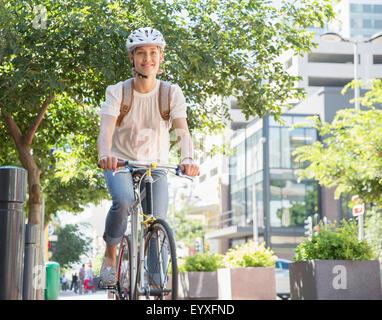 Porträt lächelnde junge Frau mit Helm Reiten Fahrrad im Stadtpark - Stockfoto