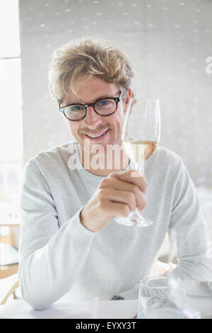 Porträt lächelnder Mann trinken Weißwein - Stockfoto