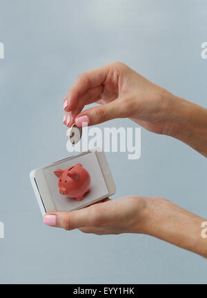 Kaukasische Frau Hinterlegung Münze in Handy-Sparschwein - Stockfoto