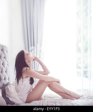 Frau am Handy auf Bett - Stockfoto