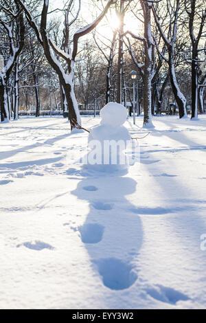 Schneemann und Fußspuren im verschneiten park - Stockfoto