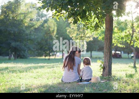 Mutter und Kleinkind sitzen unter dem Baum während der Sommerferien - Stockfoto