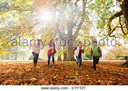 Glückliche Familie läuft durch den herbstlichen Wald - Stockfoto
