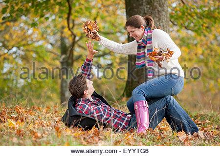 Paar spielerisch wirft Blätter im herbstlichen park - Stockfoto