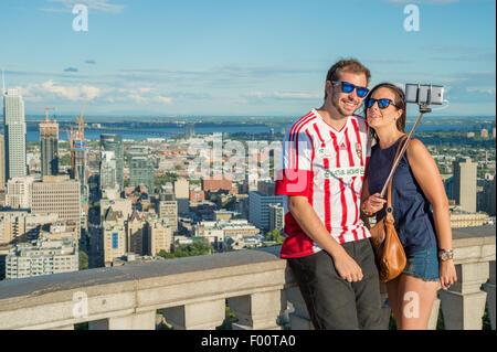 Junges Paar mit einem Selfie stick vor der Skyline von Montreal, Kondiaronk Belvedere. - Stockfoto