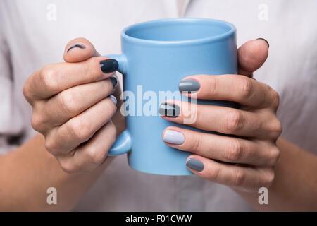 Weibliche Hände mit blauen Tasse - Stockfoto