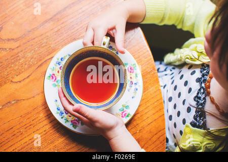 Draufsicht auf ein Mädchen sitzt am Tisch mit Wasserglas - Stockfoto