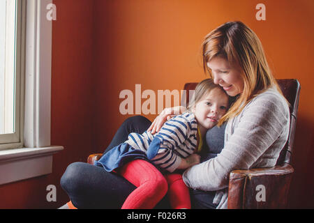 Mutter und Tochter zusammen in einem Sessel sitzend - Stockfoto