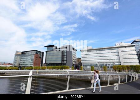 Eine Frau geht über den Fluss Clyde in Glasgow auf der Broomielaw-Tradeston-Brücke (lokal bekannt als Squiggly Brücke). - Stockfoto