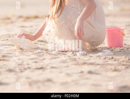 Mädchen auf der Suche nach Muscheln am Strand - Stockfoto