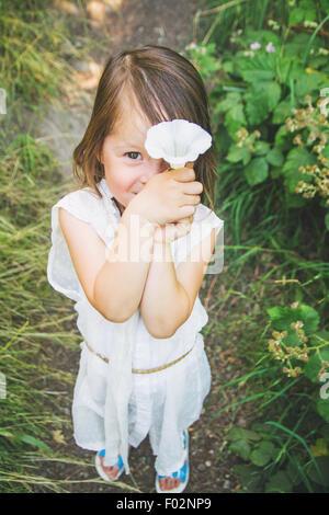 Mädchen, die eine Blume vor ihr Gesicht - Stockfoto