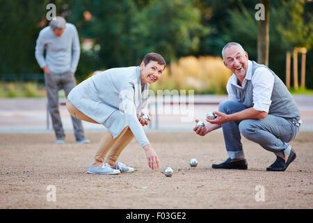 Ältere Leute spielen Boule Kugeln vom Boden anheben - Stockfoto