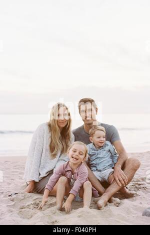 Paar sitzt mit ihrem Sohn und Tochter an einem Sandstrand am Meer, Blick in die Kamera, lächelnd. - Stockfoto
