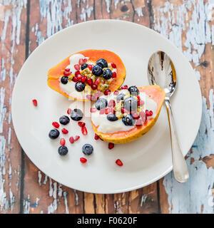 Papaya mit natürliche Soja-Joghurt und frischen Beeren, leichtes und gesundes Frühstück, Papaya, Heidelbeeren, Passionsfrucht, - Stockfoto