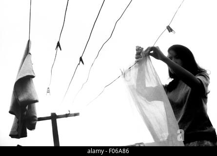 Junge Frau, die Textilien in der Sonne trocknen. - Stockfoto
