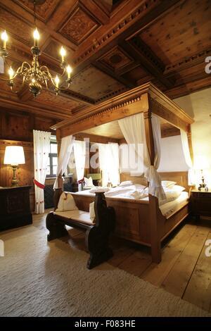 Schlafzimmer mit Himmelbett aus Holz und Kronleuchter in Hotel, Österreich - Stockfoto