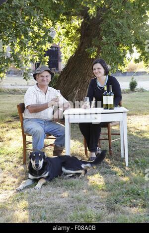 Vater und Tochter sitzen am Tisch mit Hund trinken Wein - Stockfoto
