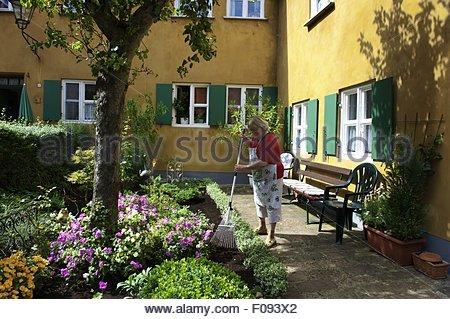 Frau im Garten bei Fuggerei soziale Wohnanlage in Augsburg, Bayern, Deutschland - Stockfoto