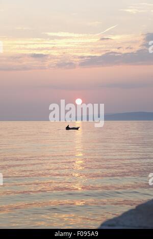 Blick auf Sonnenuntergang und Boot im Meer, Gradac, Kroatien - Stockfoto