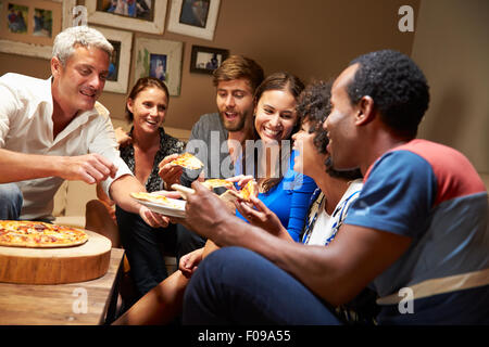 Gruppe von Erwachsenen Freunden Essen Pizza auf einer Hausparty - Stockfoto