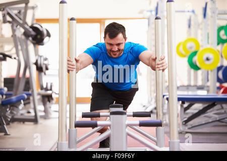 Junger Mann mit Ausrüstung in einem Fitnessstudio trainieren - Stockfoto
