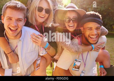 Männer geben Frau Piggybacks auf ihrem Weg zum Musikfestival - Stockfoto