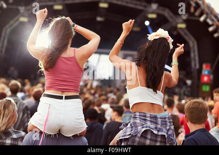 Zwei Mädchen auf Schultern in der Menge auf einem Musikfestival - Stockfoto