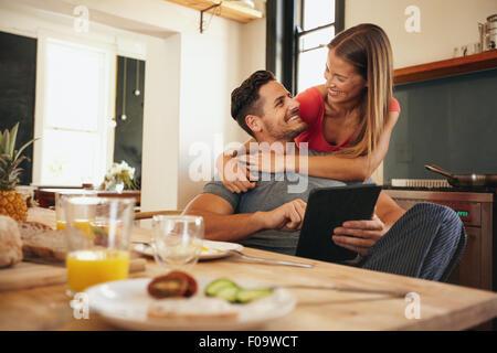 Schuss des Liebens junges Paar in der Küche mit Frühstückstisch Morgen. Mann mit digitalen Tisch, während Frau umarmt - Stockfoto