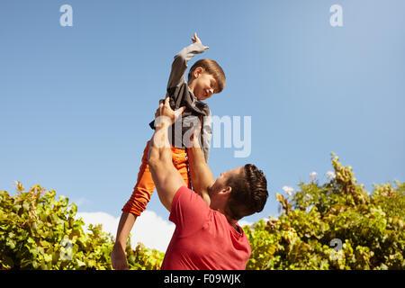 Aufnahme des jungen Mann, der seinen kleinen Sohn hoch in Luft gegen Himmel an einem sonnigen Tag hält. Glücklicher - Stockfoto