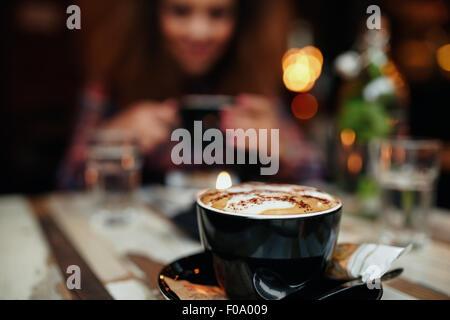 Nahaufnahme Schuss Tasse Kaffee am Tisch im Restaurant, mit einer Frau im Hintergrund. Tasse Kaffee im Fokus. - Stockfoto